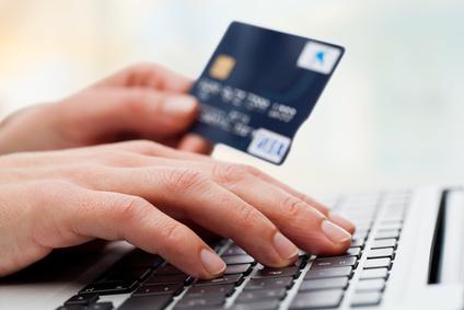 Eine Hand schreibt auf einer Tastatur. Die andere hält eine Kreditkarte.